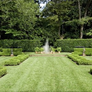 An english garden with a fountain spraying in the center